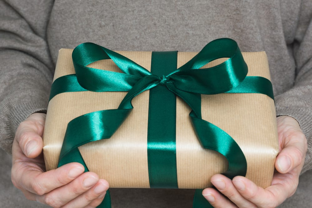 Female hands in beige sweater holding beige box wrapped in craft paper with green ribbon. Close up.